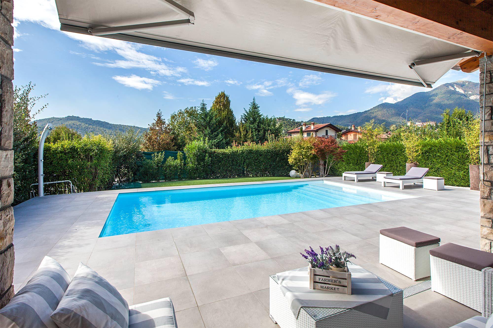 piscina a skimmer con doccia e solarium arredato