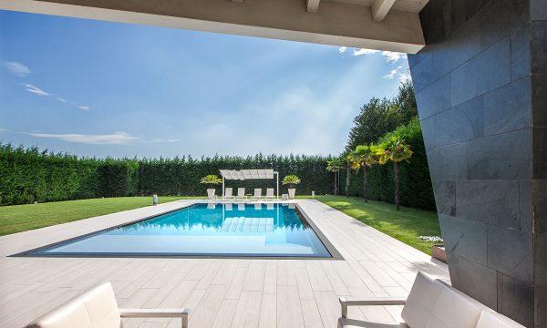 piscina interrata a sfioro con gazebo e sdraio