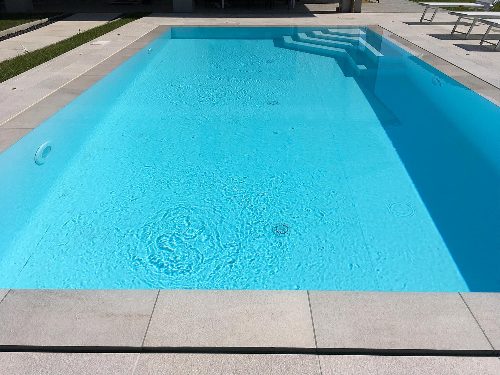 piscina a sfioro con rivestimento azzurro