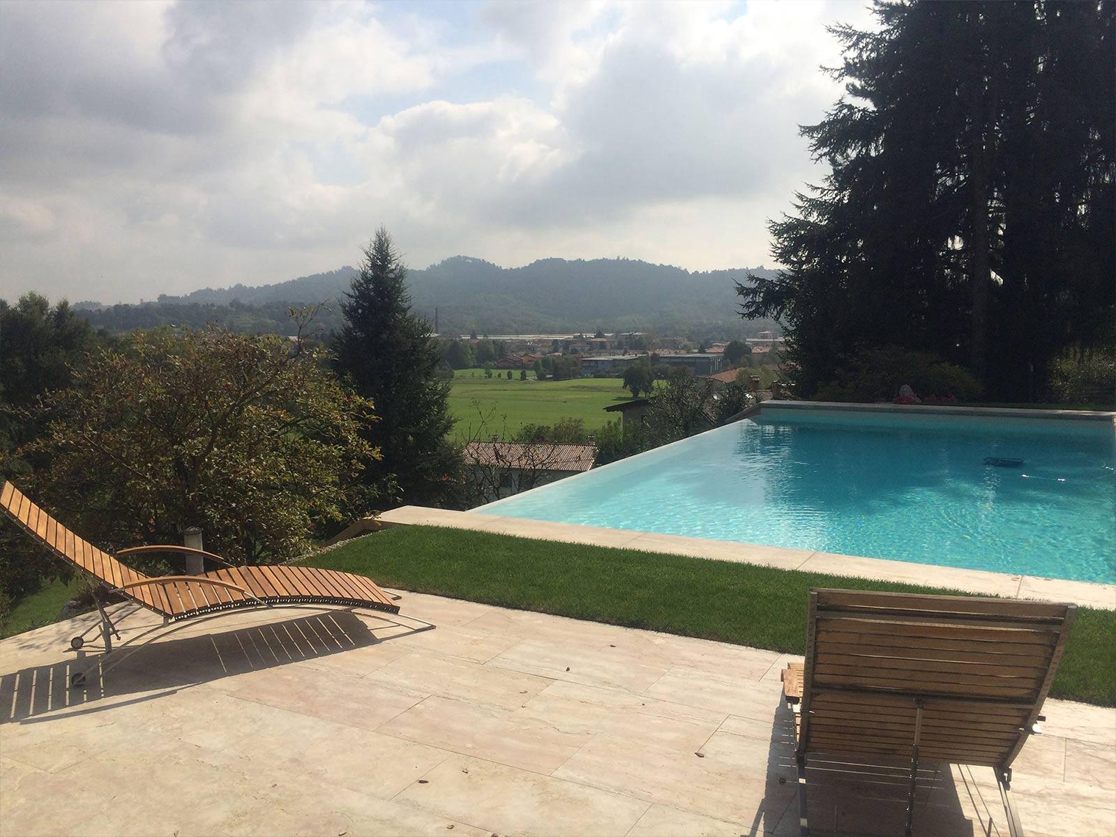 piscina a sfioro con solarium arredato