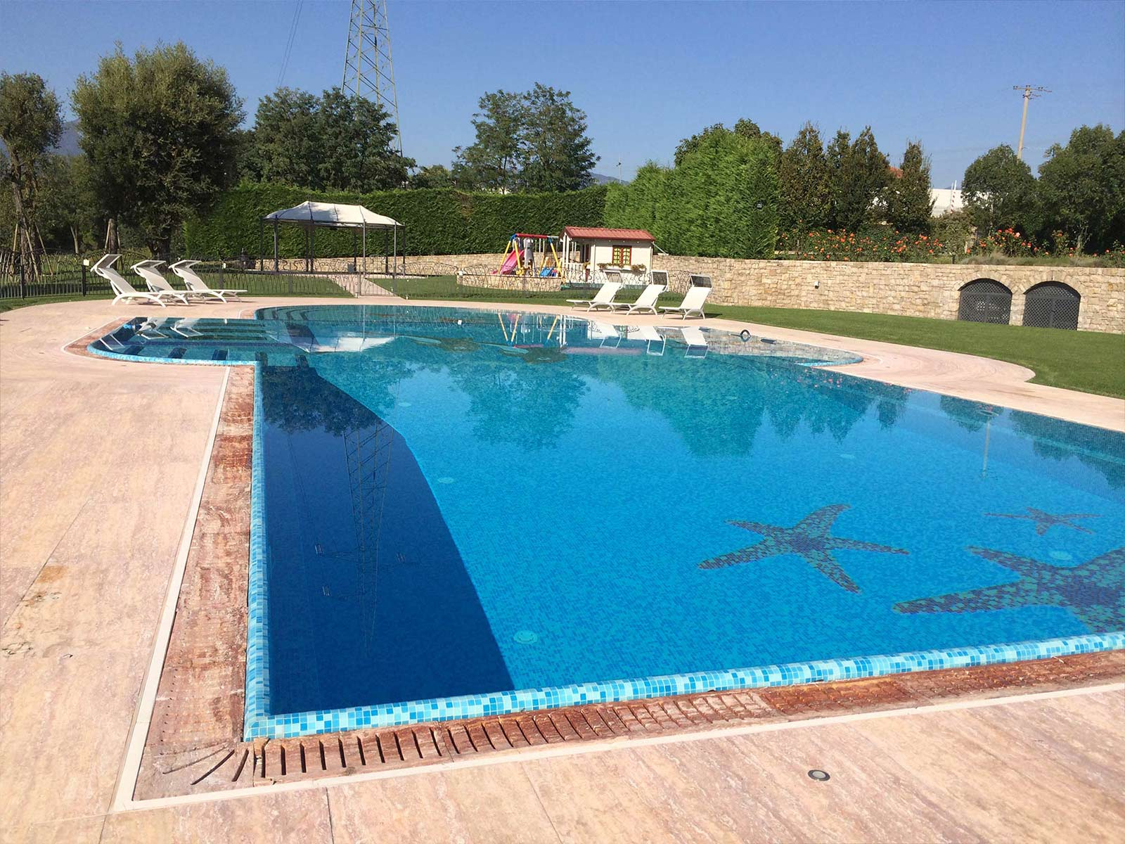 piscina a sfioro con rivestimento in mosaico